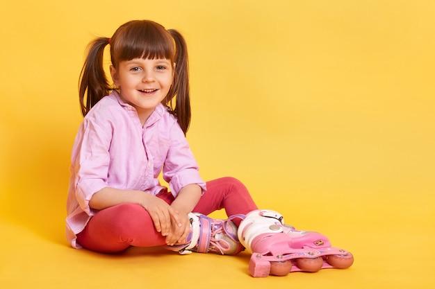 Foto de estúdio de cabelos escuros rindo menina com dois rabos de cavalo sentado