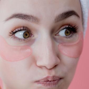 Foto de estúdio de caucasiano satisfeito sardenta mulher vestindo toalha branca na cabeça, com manchas de colágeno sob os olhos
