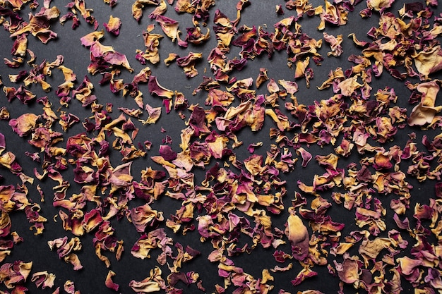 Foto de estúdio de close-up de folhas secas de chá de rosa, na mesa preta.