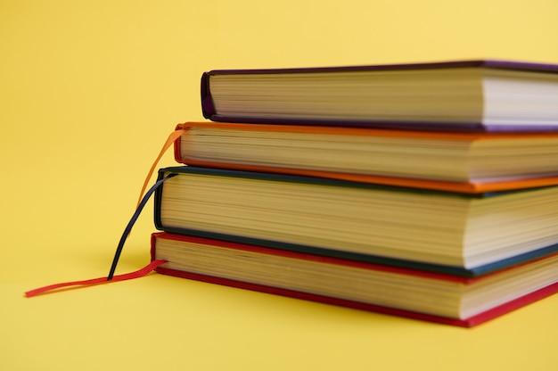 Foto de estúdio de close-up de uma pilha de livros multicoloridos sobre fundo amarelo de superfície, com espaço de cópia para o texto. conceito do dia do professor, conhecimento, literatura, leitura, erudição
