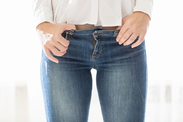Foto de estúdio de closeup de mulher sexy com corpo perfeito usando jeans azul