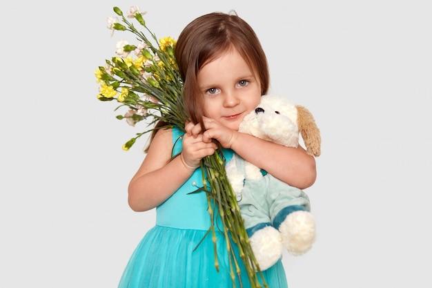 Foto de estúdio de criança atraente carrega firmemente flores e brinquedos macios, vestidos com vestido azul inchado. conceito de infância.