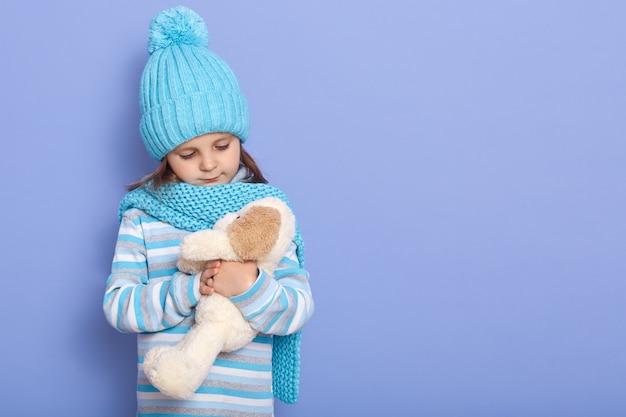 Foto de estúdio de criança feminina encantadora vestidos boné de inverno