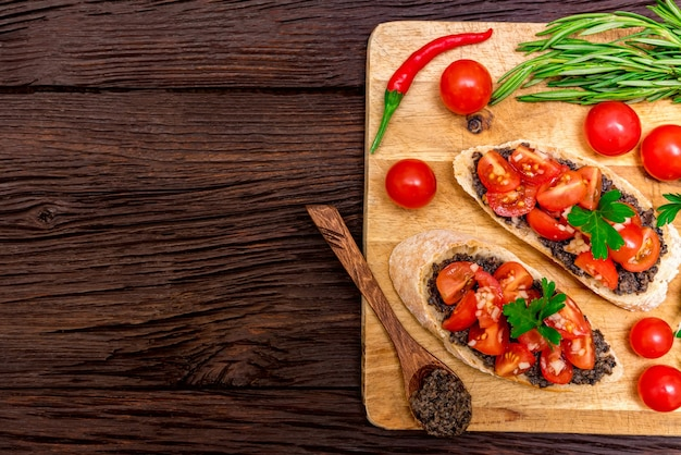 Foto de estúdio de deliciosa bruschetta italiana com patê de trufas na placa de madeira. conceito de café da manhã saudável