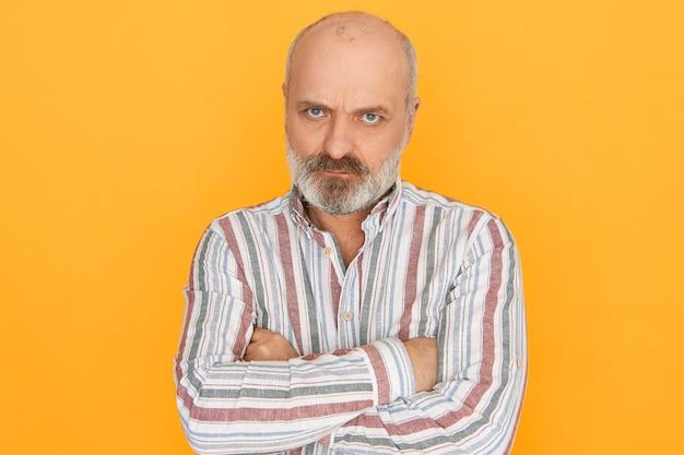 Foto de estúdio de descontente mal-humorado teimoso pensionista com espessa barba grisalha, cruzando os braços sobre o peito e olhando para a câmera por baixo das sobrancelhas, com olhar zangado