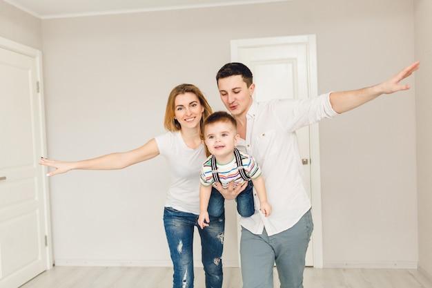 Foto de estúdio de dois pais brincando com seu filho menino.