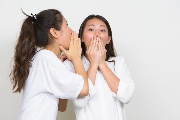 Foto de estúdio de duas jovens coreanas lindas amigas juntas contra um fundo branco
