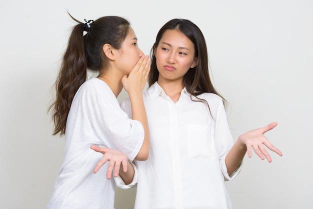 Foto de estúdio de duas jovens coreanas lindas amigas juntas contra um fundo branco Foto Premium
