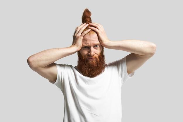 Foto de estúdio de elegante jovem hippie vestindo camiseta branca, segurando as mãos na cabeça, tendo uma expressão facial desesperada de pânico, depois que ele descobriu uma notícia terrível. cara barbudo frustrado enfrentando estresse