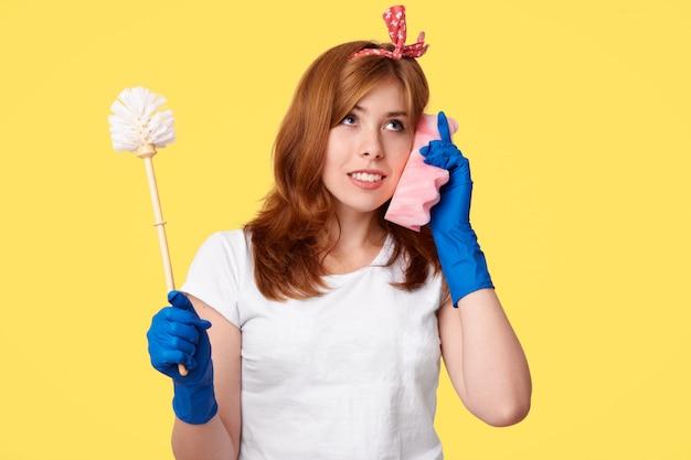 Foto de estúdio de empregada atenciosa detém escova, usa esponja como telefone celular, discute algo com amigo, vestido com roupas casuais, coloca em amarelo. conceito de limpeza e higiene