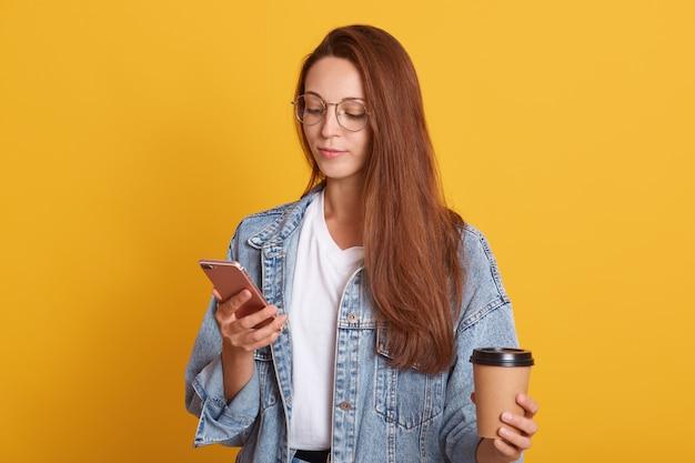 Foto de estúdio de estupefata mulher caucasiana lendo notícias no site internet enquanto bebe café para viagem