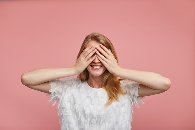 Foto de estúdio de feliz adorável jovem ruiva em uma blusa branca elegante, mantendo as palmas das mãos levantadas no rosto e sorrindo alegremente enquanto posa sobre um fundo rosa