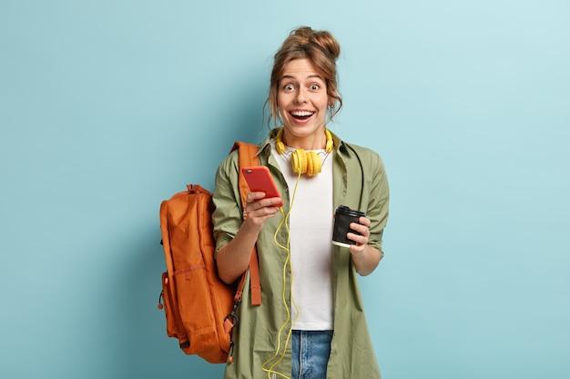Foto de estúdio de feliz garota hipster segurando um celular moderno, verifica a notificação, conectado a fones de ouvido estéreo
