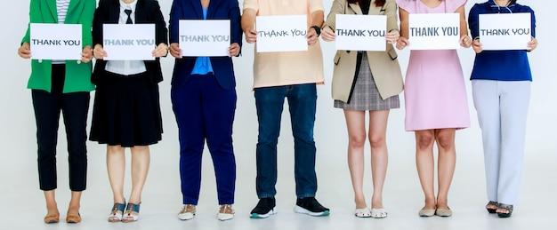 Foto de estúdio de fontes de variedade, letras de agradecimento, sinal de papel segurando por funcionários sem rosto não identificados e irreconhecíveis no negócio usa estande mostrar apreciação aos clientes no fundo branco.