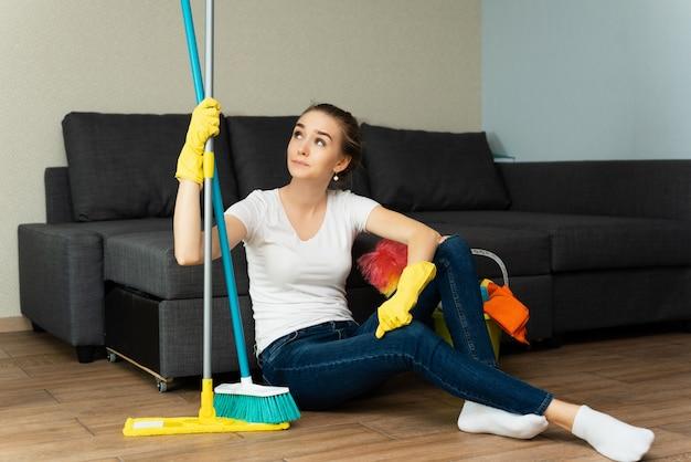 Foto de estúdio de garota bonita infeliz com expressão dolorosa no rosto, como ela tem que ficar em casa e ajudar a mãe a limpar os quartos em vez de sair com os amigos