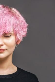 Foto de estúdio de garota com um belo penteado rosa, batom vermelho nos lábios, fica de olhos fechados. copie o espaço
