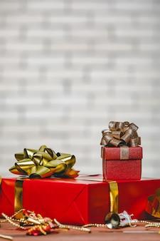 Foto de estúdio de grande papel vermelho embrulhado presente presente com laço de fita de ouro e prata e pequenas caixas de suspensão de maquete decorativas colocadas na mesa de madeira em frente à parede de tijolo branco fundo desfocado.