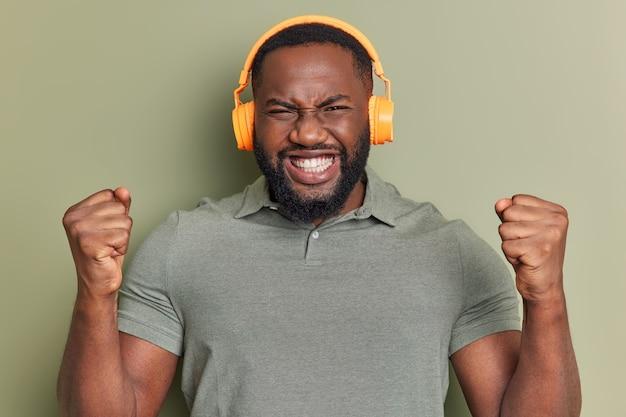 Foto de estúdio de homem com barba espessa levanta clenche? punhos celebra o sucesso parece que o vencedor usa fones de ouvido estéreo ouve música poses dentro de casa