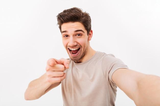 Foto de estúdio de homem positivo em camiseta casual e cerdas no rosto, sorrindo e apontando o dedo na câmera enquanto estiver a tomar selfie, isolado sobre a parede branca