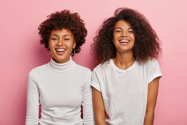 Foto de estúdio de irmãs afro-americanas felizes desfrutando de um bom momento, use roupas casuais brancas, sorria amplamente, divirta-se juntas durante o tempo livre, isoladas sobre uma parede rosa.
