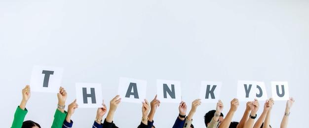 Foto de estúdio de irreconhecível grupo não identificado de oficial de equipe no escritório corporativo, segurando o sinal de papelão, obrigado alfabeto, sobre a cabeça, mostrando apreço ao cliente no fundo branco.