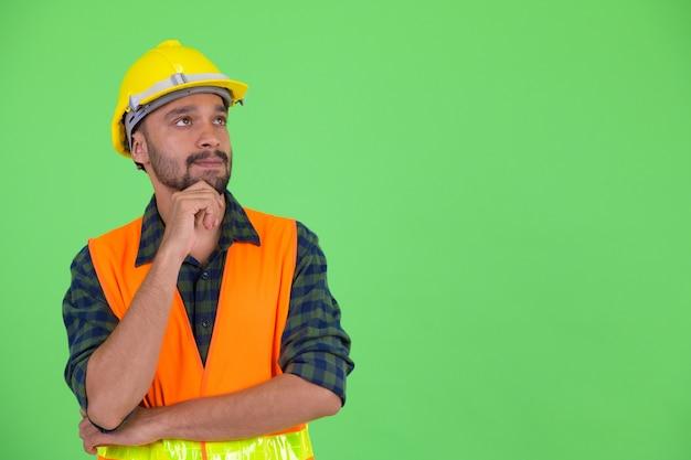 Foto de estúdio de jovem bonito barbudo persa trabalhador da construção civil contra chroma key com fundo verde