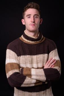 Foto de estúdio de jovem bonito com suéter de gola alta pronto para o inverno contra um fundo preto