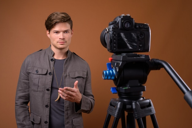 Foto de estúdio de jovem bonito fazendo um vlog com a câmera