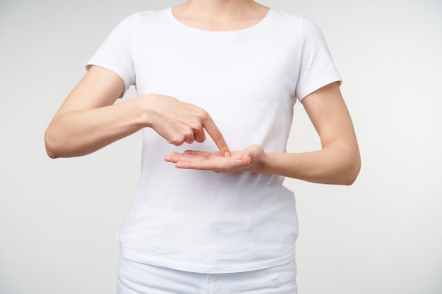 Foto de estúdio de jovem com manicure nua, mantendo o dedo indicador na palma da mão levantada, enquanto mostra a escrita na linguagem de sinais, em pé sobre um fundo branco
