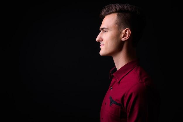 Foto de estúdio de jovem empresário bonito de camisa vermelha contra um fundo preto