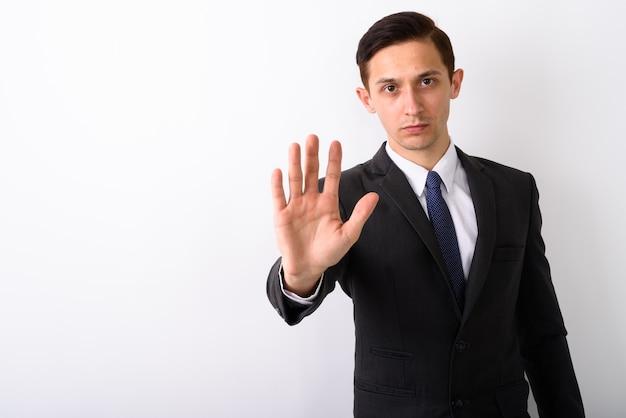 Foto de estúdio de jovem empresário bonito mostrando sinal de mão parada