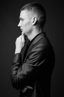 Foto de estúdio de jovem empresário vestindo terno contra uma parede cinza