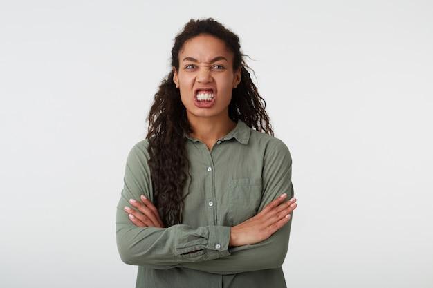 Foto de estúdio de jovem estressada mulher encaracolada de cabelos escuros com penteado casual, mostrando os dentes enquanto faz uma careta no rosto e mantém as mãos cruzadas, isolado sobre fundo branco