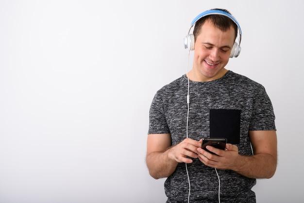 Foto de estúdio de jovem feliz musculoso sorrindo e ouvindo