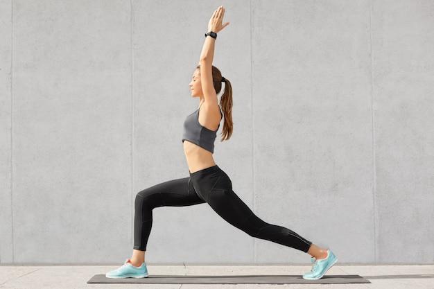 Foto de estúdio de menina magro bate palmas, faz exercícios de equilíbrio do braço, trabalha no interior do loft, mantém a dieta, tem estilo de vida saudável