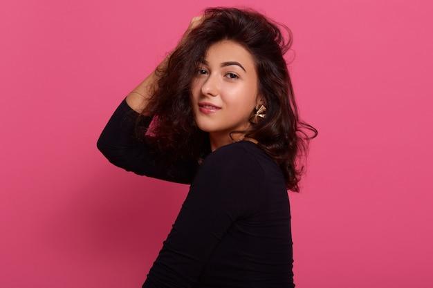 Foto de estúdio de menina sorridente com cabelos escuros e aparência agradável