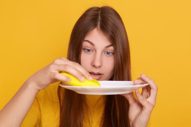 Foto de estúdio de menina surpresa com prato sujo e esponja nas mãos