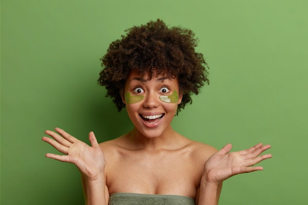Foto de estúdio de mulher alegre espalha as palmas das mãos e reage alegremente a algo aplica manchas de colágeno sob os olhos reduz o inchaço e as rugas isoladas na parede verde do estúdio