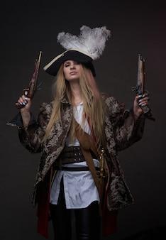 Foto de estúdio de mulher atraente pirata com armas e tricórnio contra um fundo escuro.