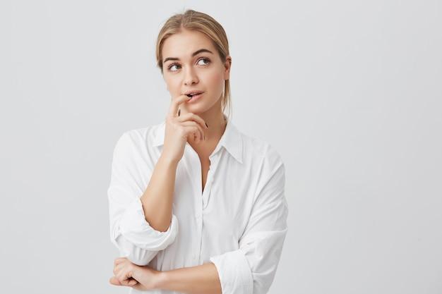Foto de estúdio de mulher bonita astúcia com cabelo loiro liso, olhando de lado, segurando a mão sob o queixo, com a intenção de realizar um plano complicado.