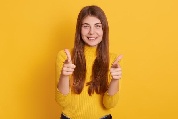 Foto de estúdio de mulher caucasiana jovem bonita, apontando para a câmera com os dedos indicadores