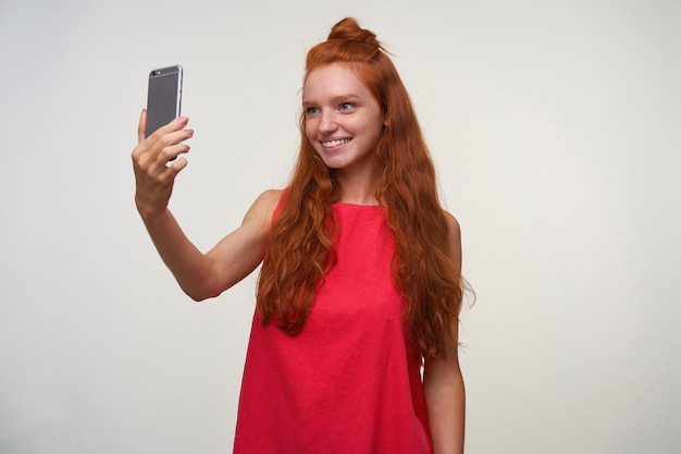 Foto de estúdio de mulher com cabeça de leitura jovem positiva com cabelo ruivo ondulado posando sobre fundo branco sem maquiagem, fazendo selfie em seu smartphone em um vestido rosa casual