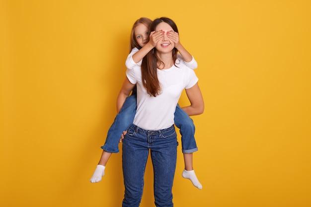 Foto de estúdio de mulher dando carona piggy indoor, feminino vestindo jeans e camiseta casual branca