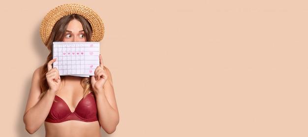 Foto de estúdio de mulher europeia atordoada detém calendário de período, rosto de contras, vestido de maiô, surpreendeu a expressão, fica em bege com espaço de cópia para o seu anúncio