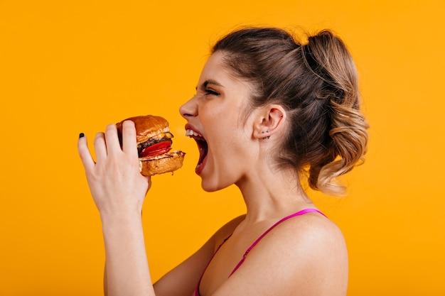 Foto de estúdio de mulher faminta com sanduíche