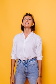 Foto de estúdio de mulher feliz, cabelo curto, vestindo camisa branca e calça jeans, posando na parede amarela