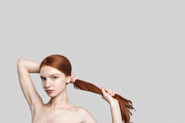Foto de estúdio de mulher jovem e confiante ruiva segurando seu cabelo longo e sedoso na mão em pé contra um fundo cinza. cuidado capilar. conceito de beleza