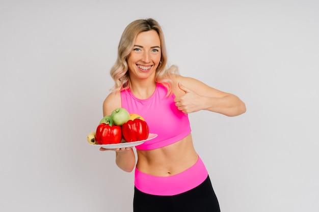 Foto de estúdio de mulher jovem fitness em uma roupa esportiva segurando maçã verde, frutas, legumes.