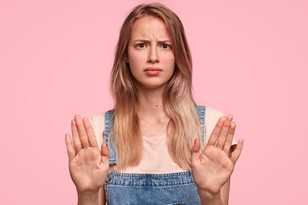 Foto de estúdio de mulher jovem mal-humorada com expressão irritada