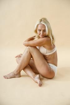 Foto de estúdio de mulher loira madura posando de cueca, sentada no chão e olhando para baixo